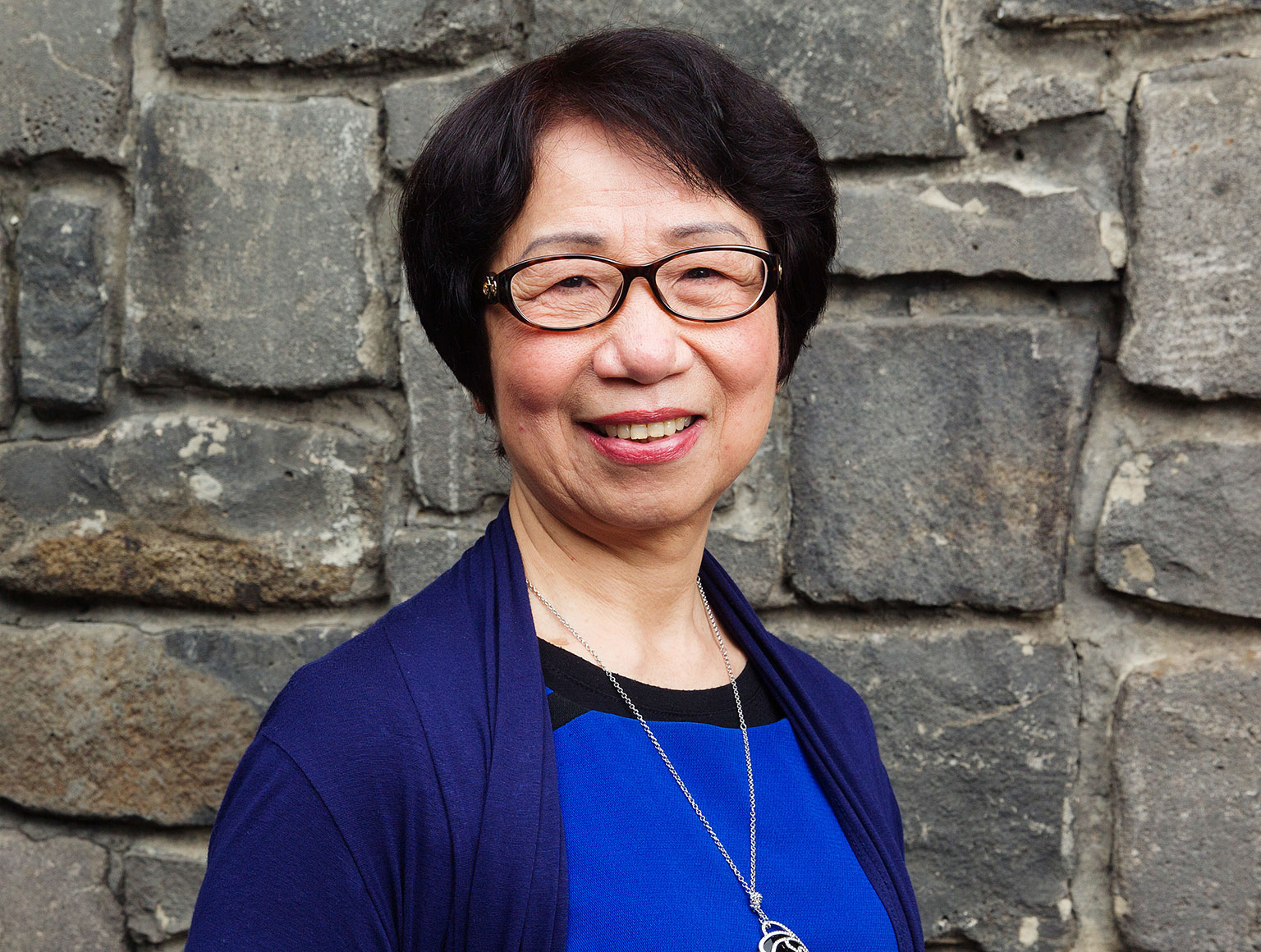 Kim Vu, counsellor with the Australian Vietnamese Women's Association's Gambling Counselling Program, poses for photo in front of bluestone wall