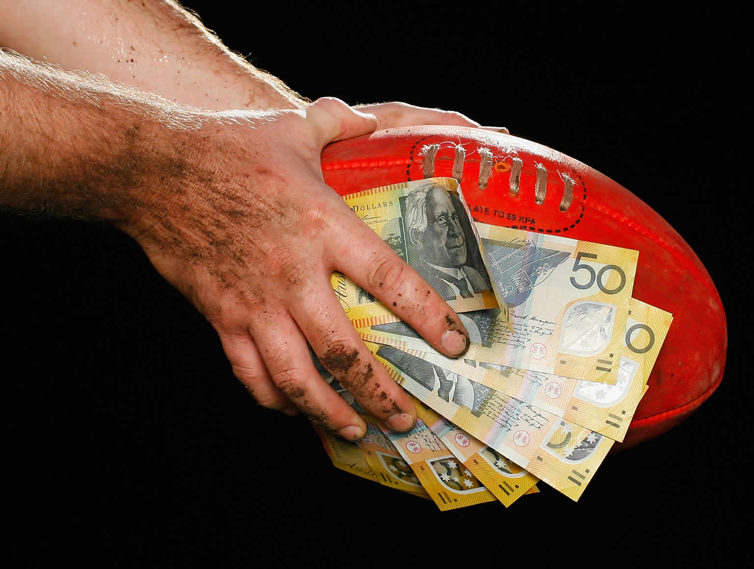 Hands covered in dirt holding a football with a bunch of $50 notes