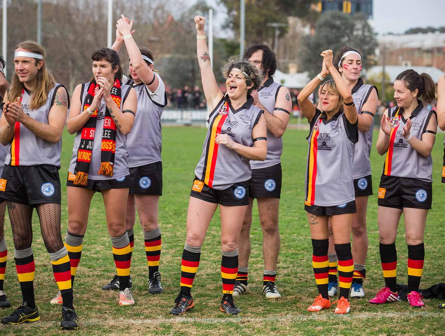Photo of four male footballers and six female footballers from the same team, standing in a football field clapping and cheering towards a point left of the camera, a crowd along the boundary can be seen in the background.