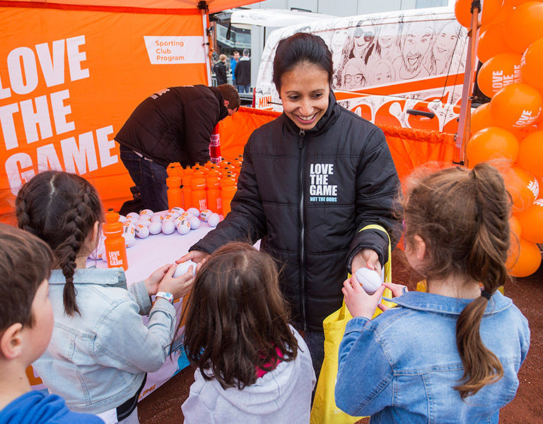 Photo of a smiling woman with tied-back dark hair handing miniature white AFL footballs to four children seen from behind, the interior of a bright orange marquee in the background, with a table with footballs and orange drink bottles on it, LOVE THE GAME emblazoned on the back wall, and bright orange balloons to the right.