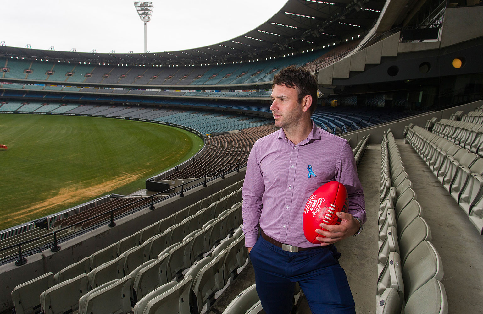 Brent Guerra holding a football in the stands of the MCG