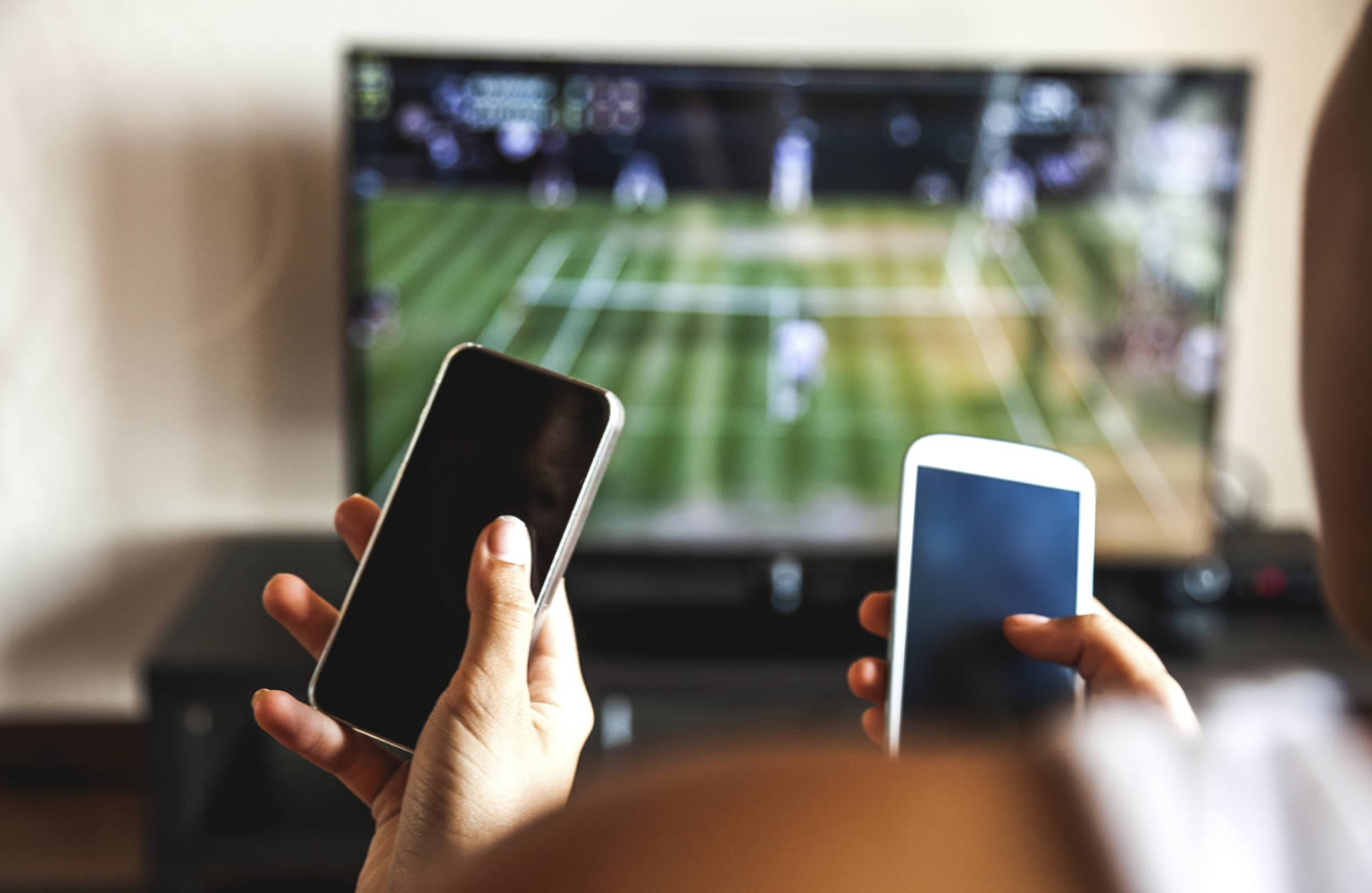 Two people in front of television showing tennis match in progress and both are holding mobile phones in front of them.