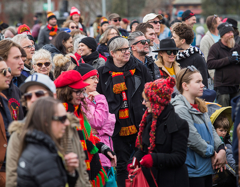 Photo of a crowd of people standing outside, wearing warm coats, bright scarves and beanies.