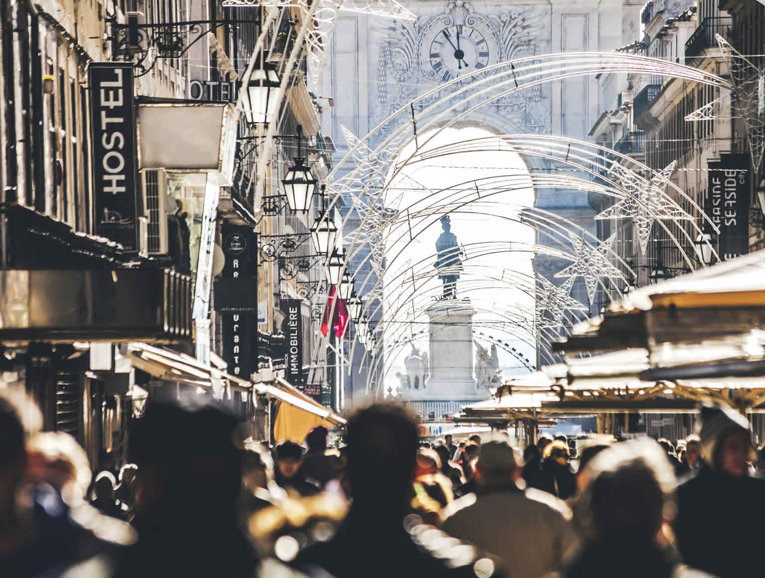 Crowded main street in Baixa, Lisbon, Portugal. Shops, people, and a statue under an arch with an ornate clock