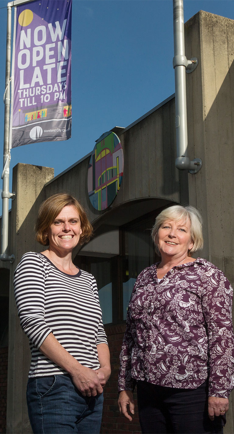 Photo of two women standing outside on a sunny day, smiling, a concrete building façade behind them, with a bright banner on a pole that says: Now open late, Thursdays till 10 pm, Moreland City Council