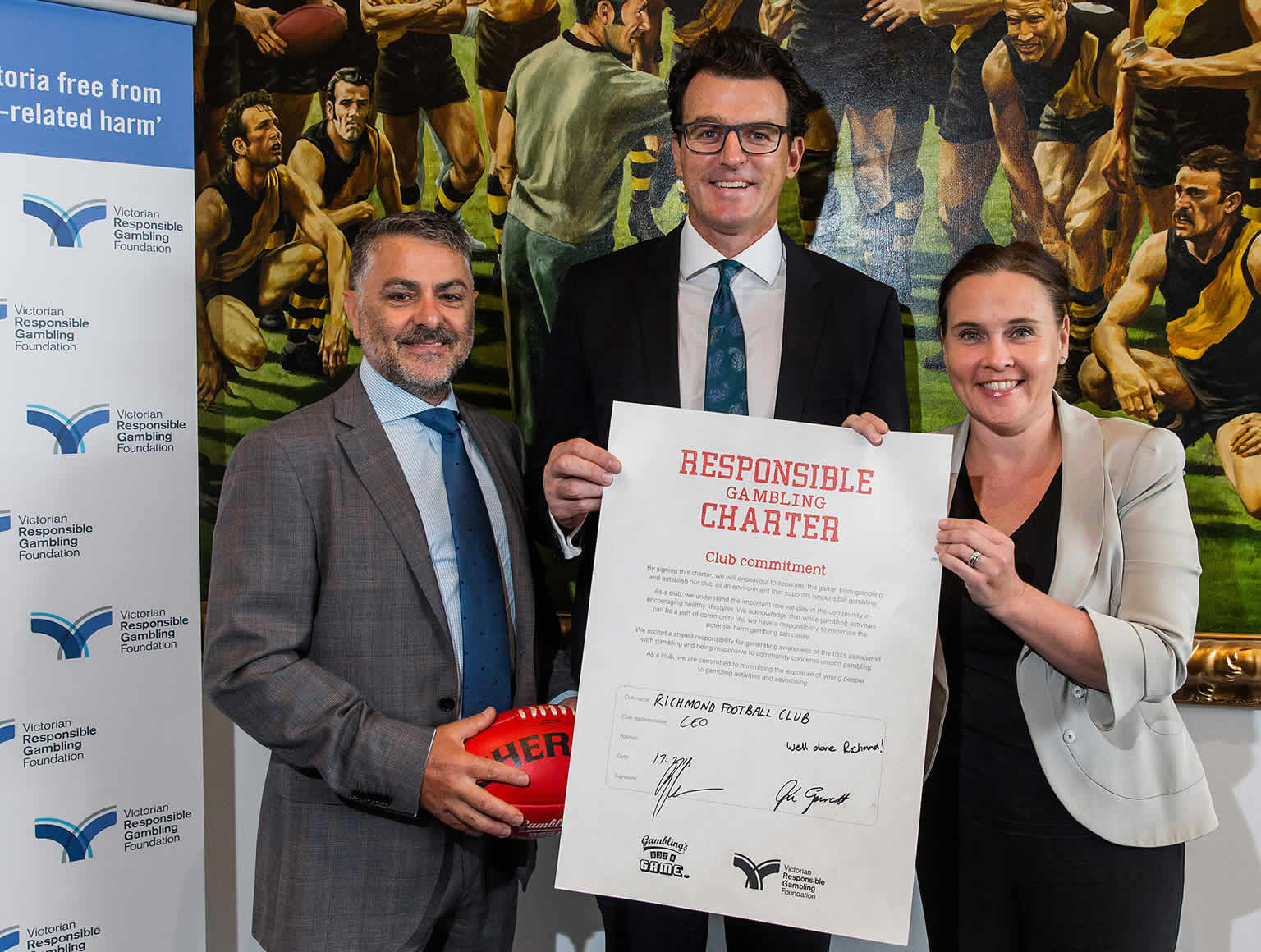 Victorian Responsible Gambling Foundation CEO Serge Sardo, Richmond CEO Brendon Gale and Minister for Gaming and Liquor Regulation Jane Garrett hold a signed Responsible Gambling Charter standing in front of painting of Richmond players.