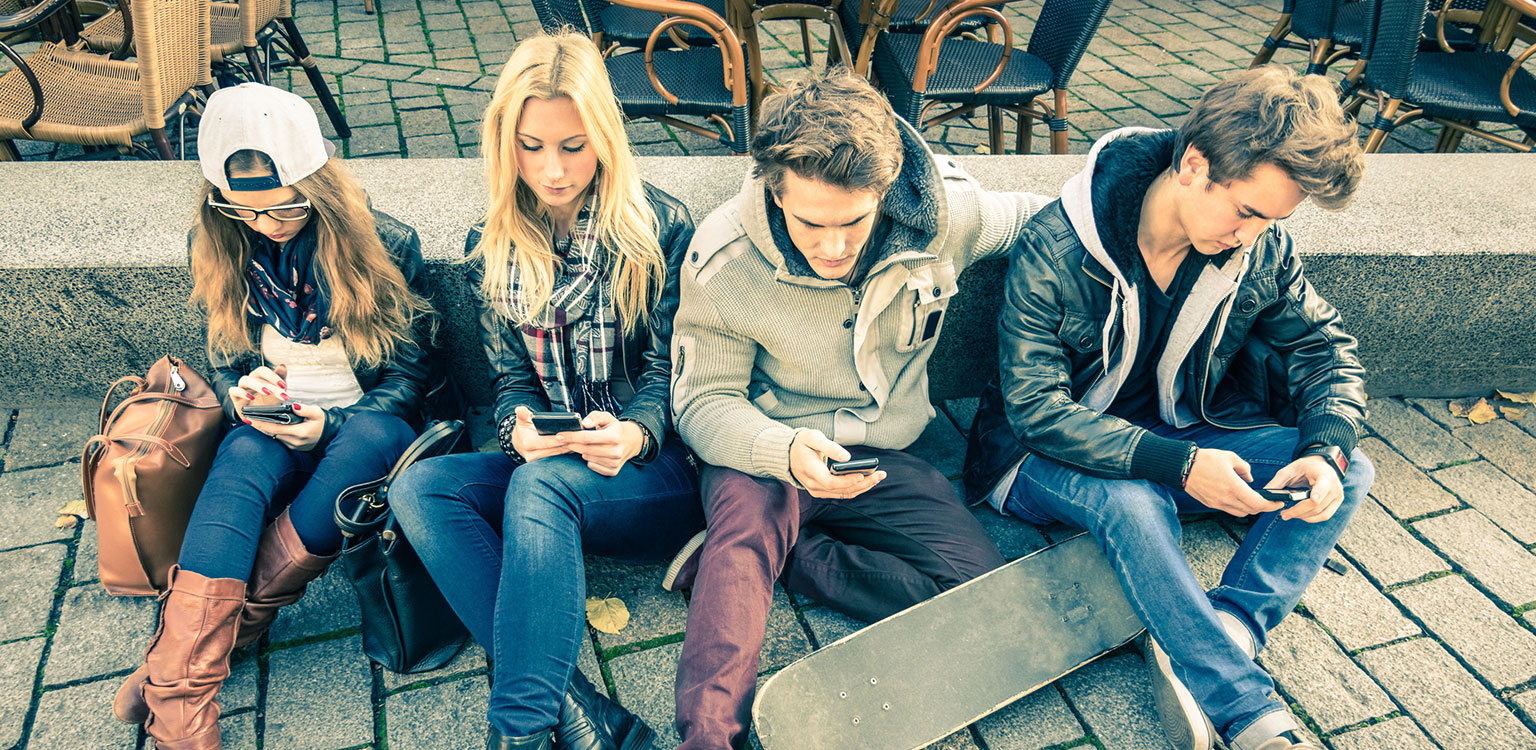 Four tennagers playing on their mobile phones beside a café