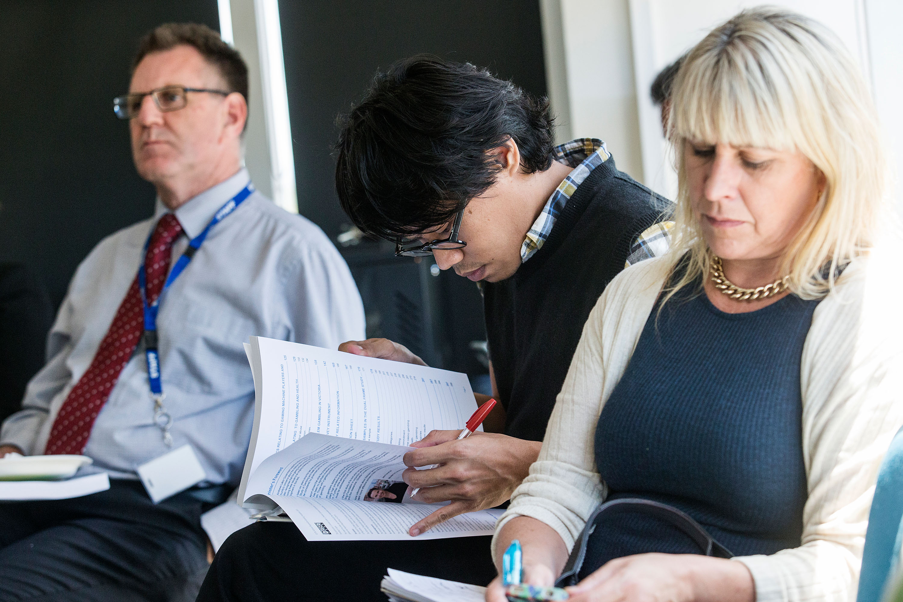 Man looking ahead and man and woman reading report at Prevalence study launch