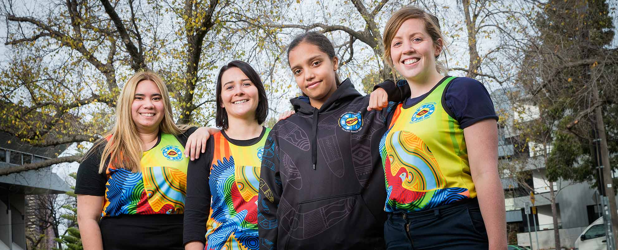 Photo of four smiling young women, standing with arms around each other's shoulders, three wearing brightly coloured singlets with an Indigeneous bird design, the other wearing a dark hooded sweater with Indigeneous designs,  in a park with autumn trees towering above them.