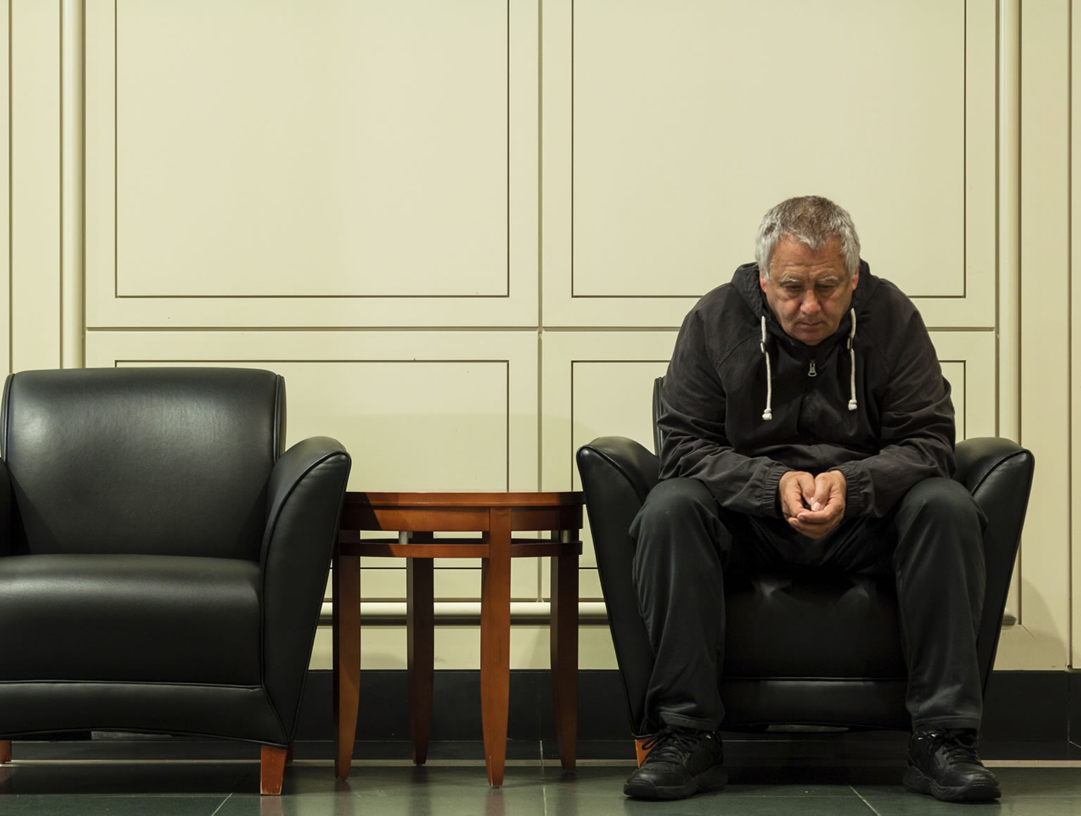 Man sitting alone in large room looking at floor