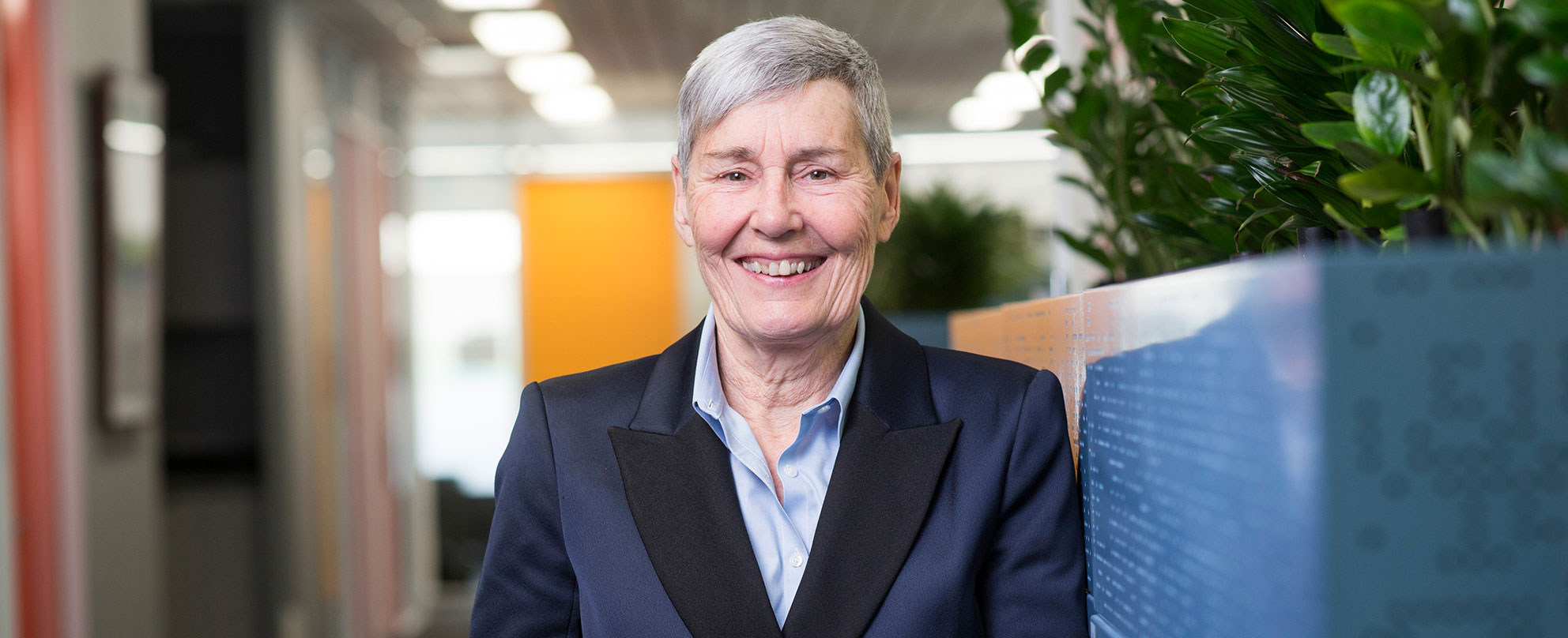 Photo of a smiling older woman with short grey hair wearing a navy blazer and pale blue shirt, brightly coloured and lit office environment in background.