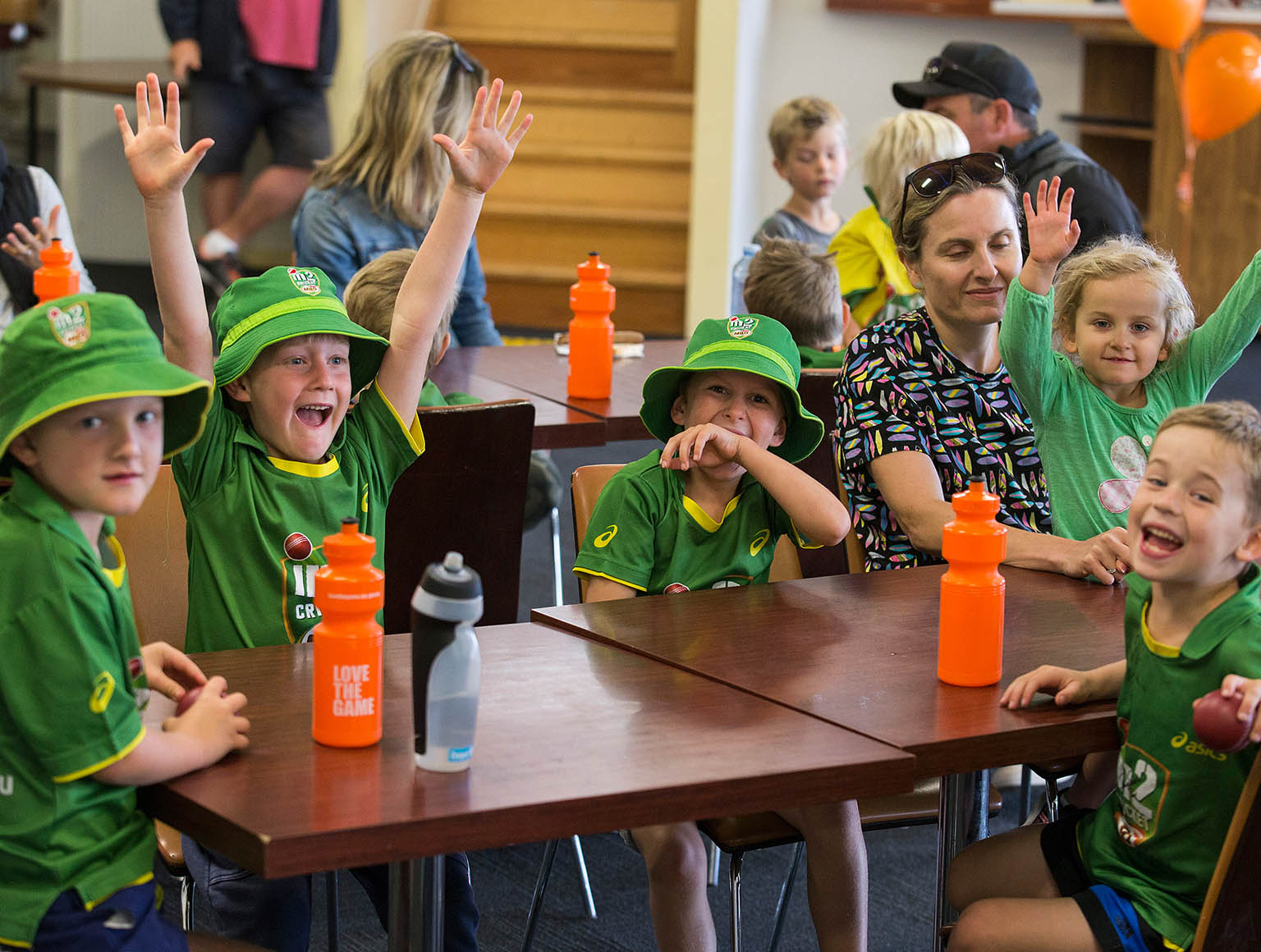 Five young boys in green and gold cricket gear sitting laughing at a table with a woman and her young daughter