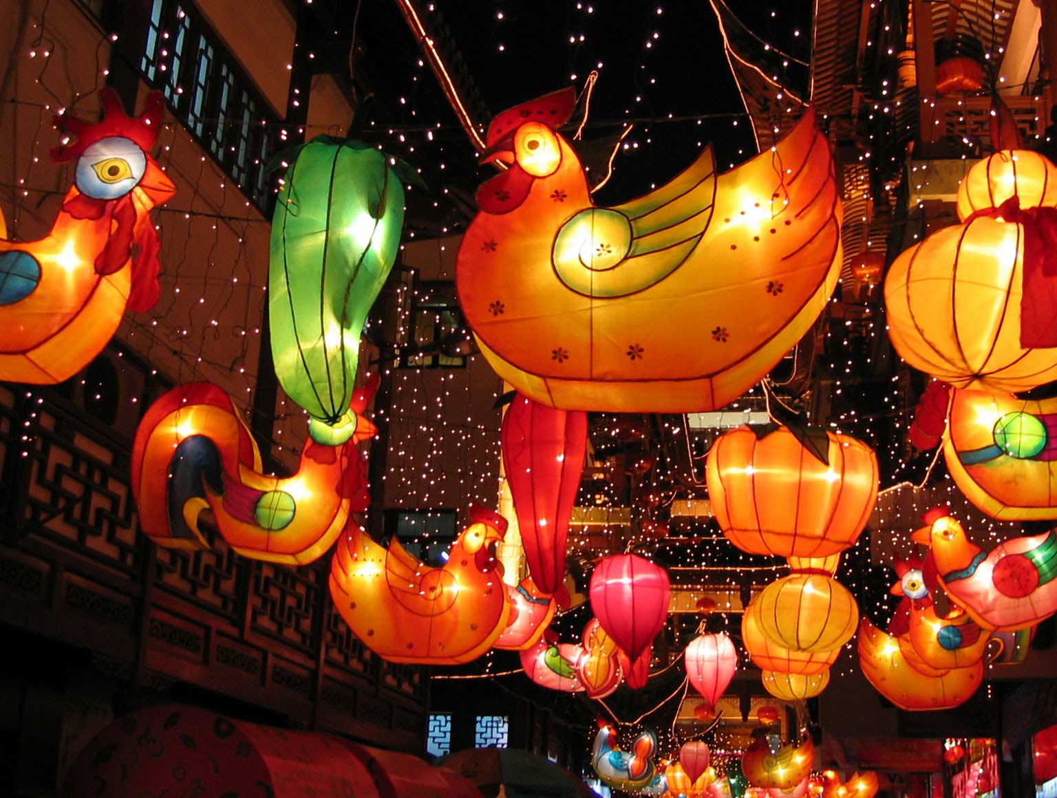 Chinese lanterns in the shape of roosters against a night sky