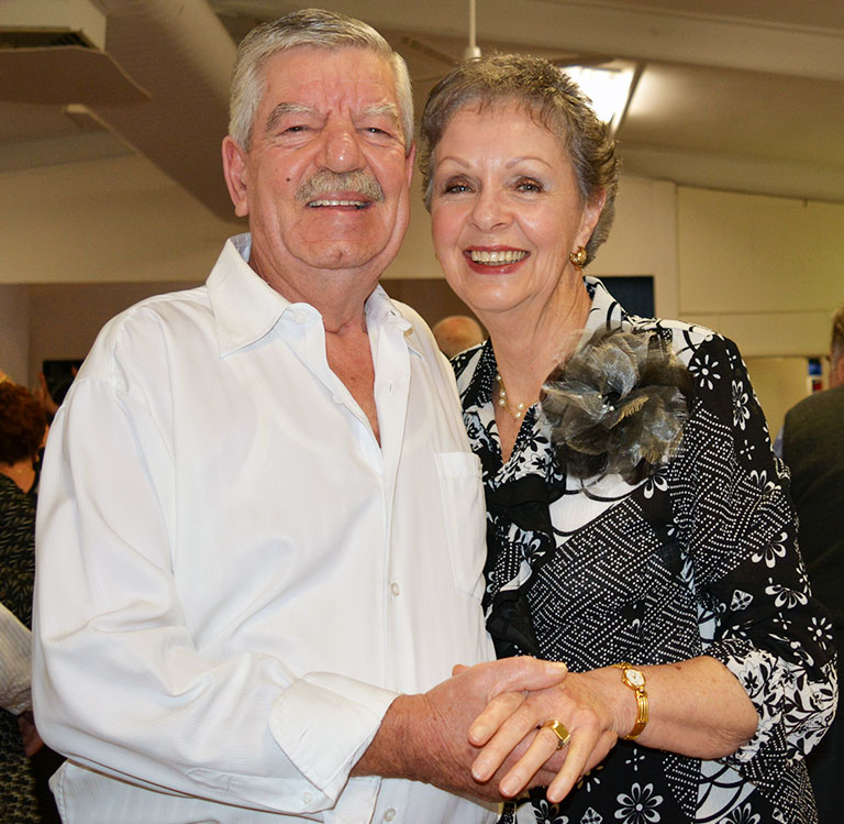 Older man and woman holding hands and smiling at an indoor event