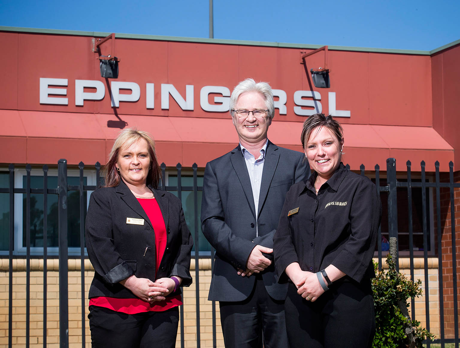 Two women and a man standing in front of building with an Epping RSL sign