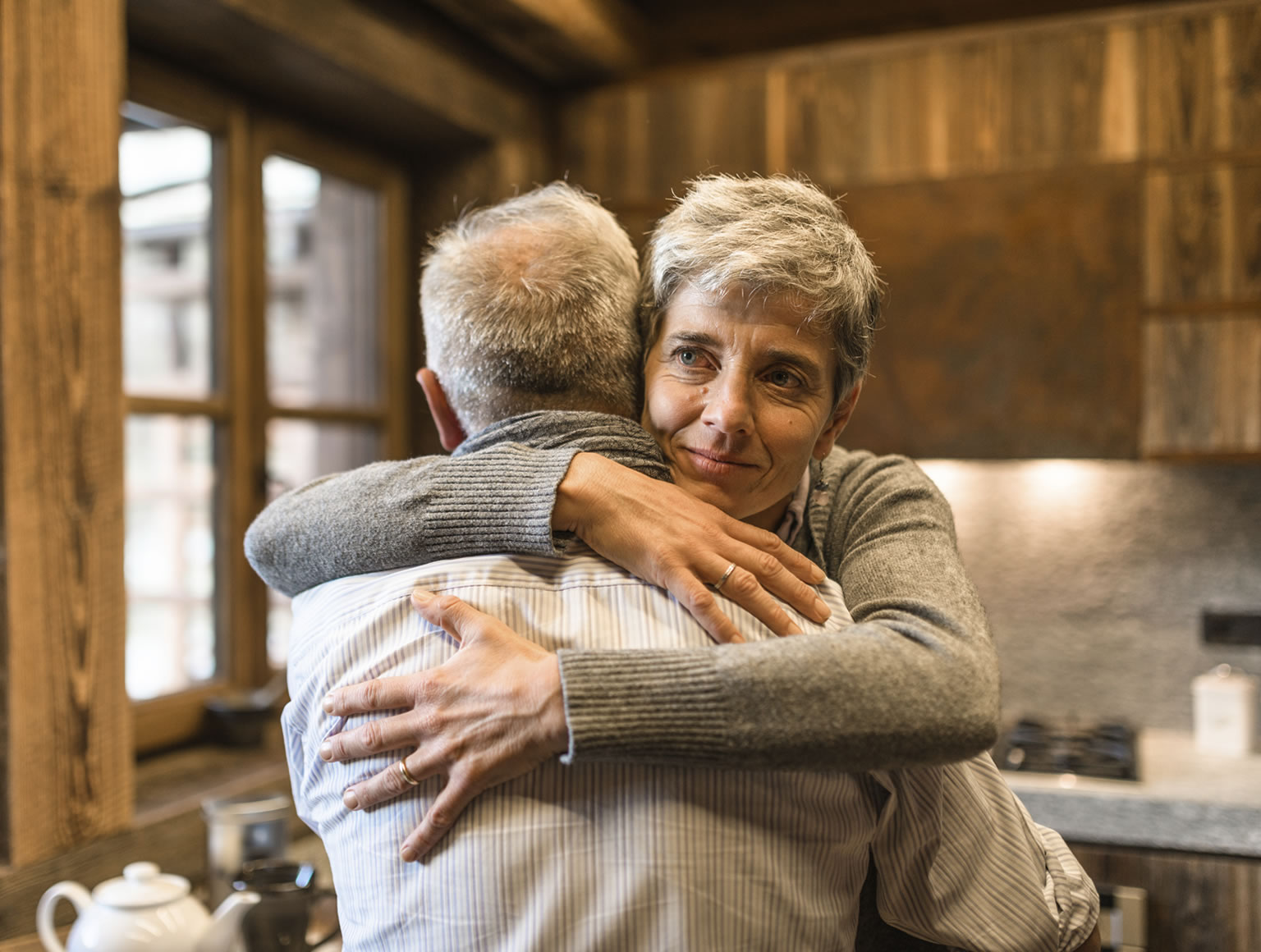 Older couple embracing in family kitchen