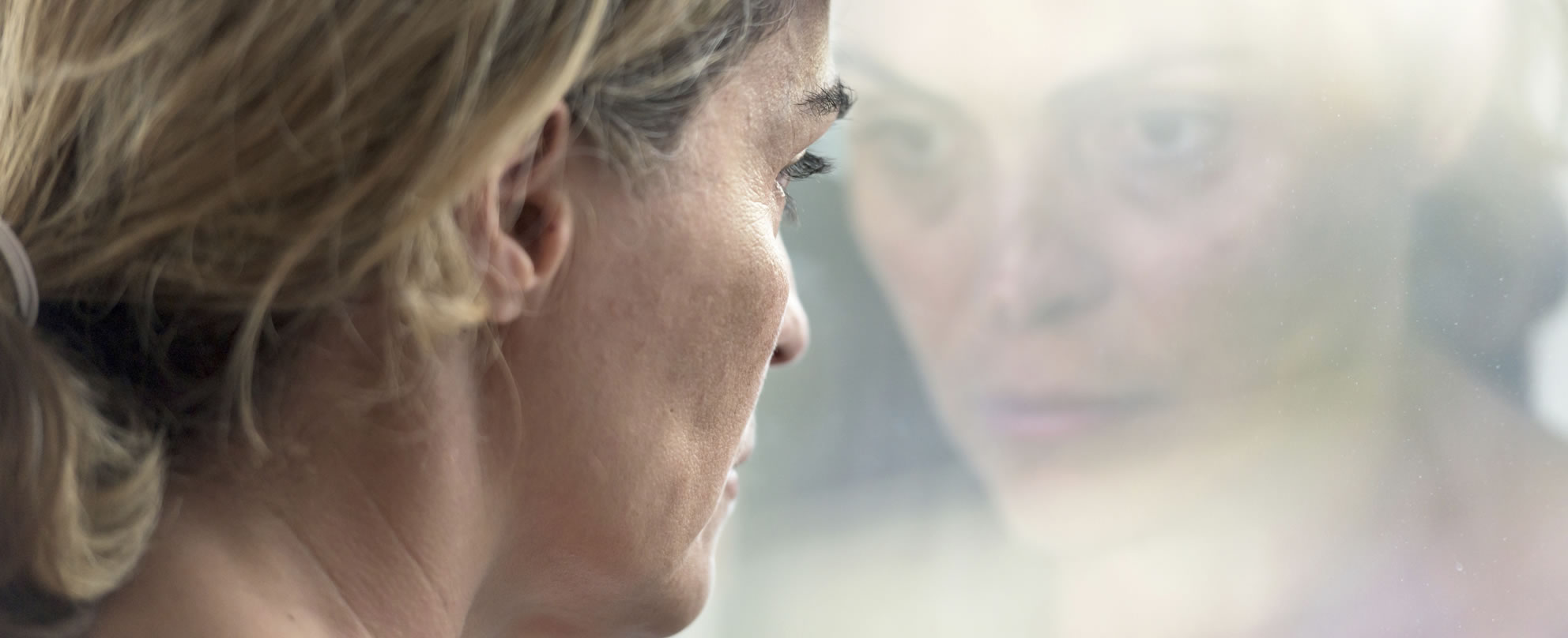 A woman looks despondently out a window that is reflecting her face