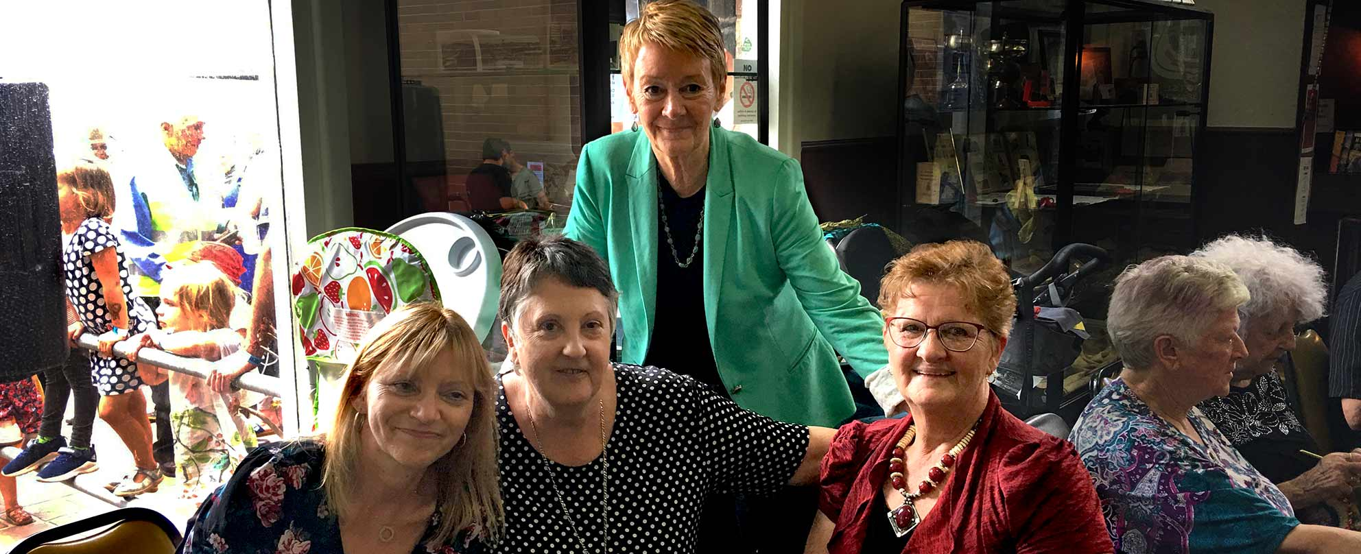 Photo of four smiling middle-aged women in a pub environment, three sitting at a table and one standing behind them.