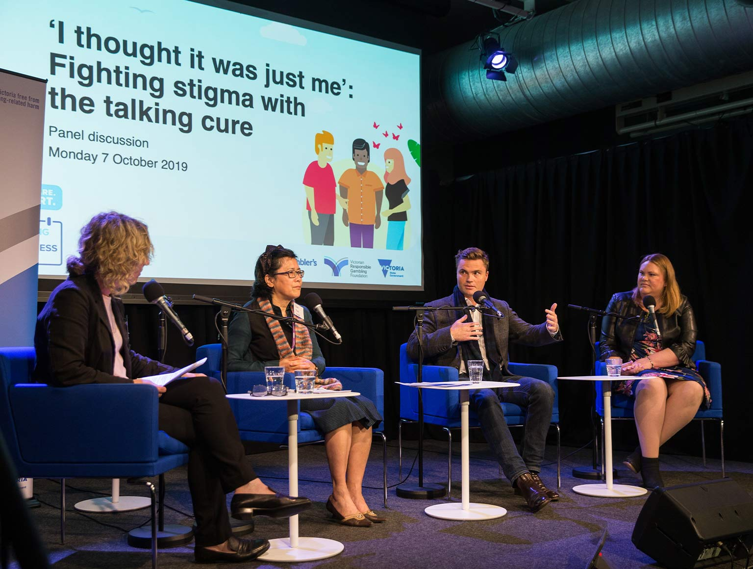 Photo of three women and one man seated on a stage, talking. Behind them a projected screen says: 'I thought it was just me': fighting stigma with the talking cure, Panel discussion, Monday 7 October 2019.