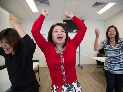 Three Vietnamese women in a large room, with joyous expressions and their arms in the air
