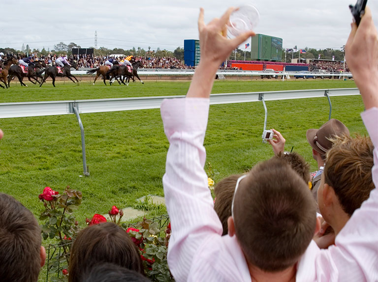 Man holds arms up as horses cross finish line at racetrack