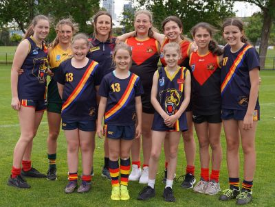 Photo of a young woman (standing in back row) with nine girls, all smiling at the camera, dressed in blue, red and yellow football guernseys and shorts on a grassy oval, trees and buildings in the background.