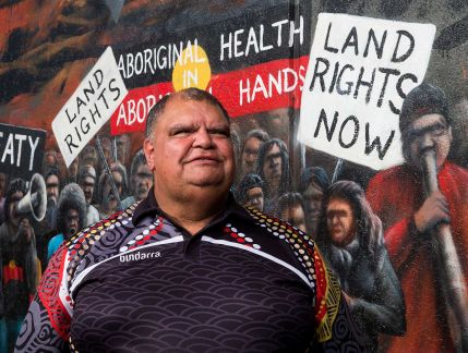 Photo of a middle-aged Aboriginal man, smiling beyond the camera, wearing a brightly coloured polo shirt with stylised details of an Aboriginal painting, standing in front of a mural featuring signs that say: Treaty, Land rights, Aboriginal health in Aboriginal hands, Land rights now.