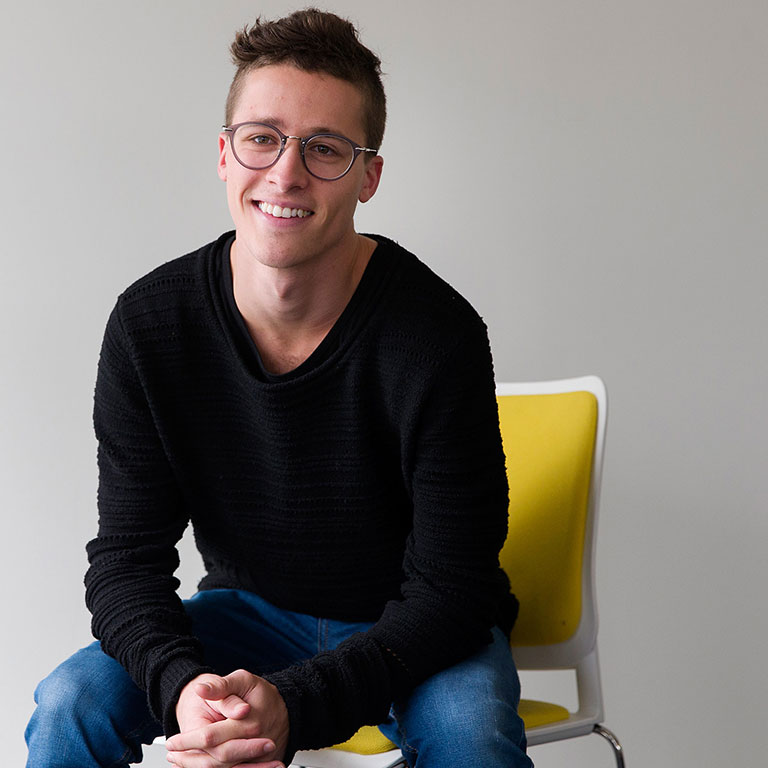 Cover story author Jake posing for photo in chair