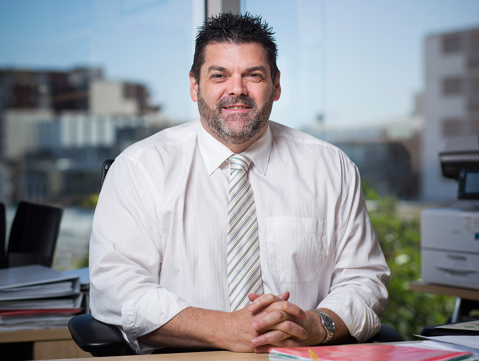 A man in a business shirt and tie sitting in and office with a city view behind him