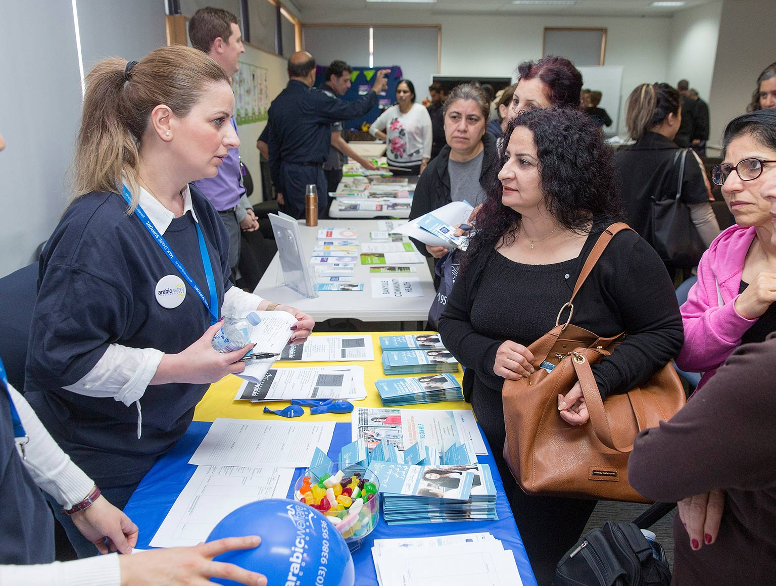 Two young women, one wearing a hijab and the other with a pony tail and an Arabic Welfare badge, speaking to a group of older women over an information table with brochures, people clustered around other tables with brochures in background.