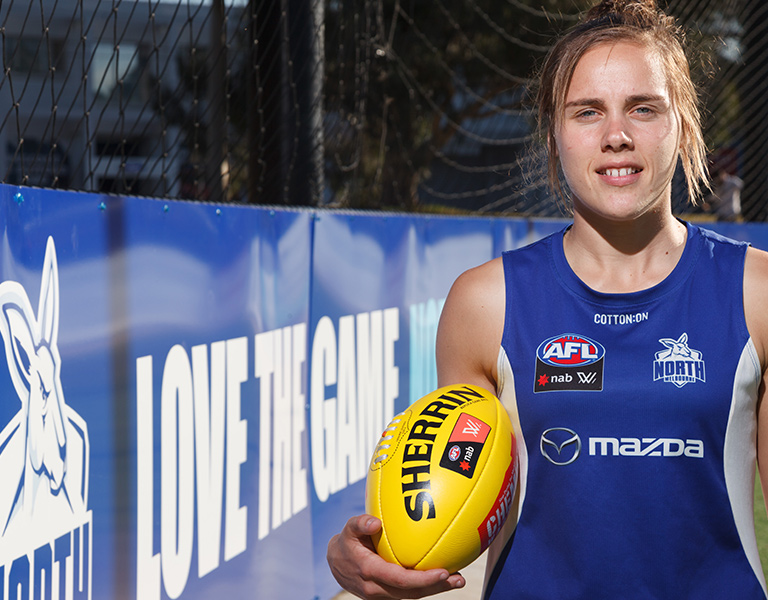 Photo of a young woman with light brown hair tied up, wearing a blue and white North Melbourne Football Club singlet, holding a yellow AFL football, looking at the camera with an intense expression, a banner to the right says 'Love the game