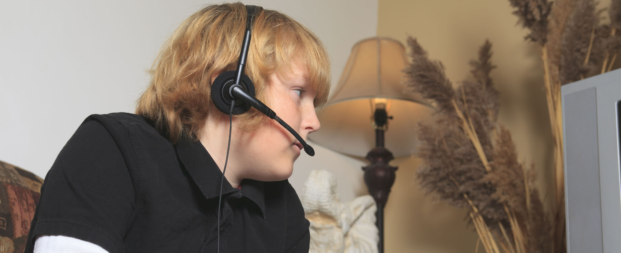 Teenage boy sitting wearing headset and facing screen engaged in online gaming