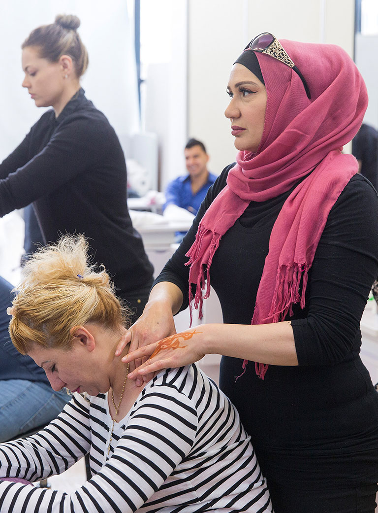 Photo of a woman wearing a pink hijab massaging the shoulders of a seated woman in a striped top with blonde hair pinned up, another masseur at work next to them, and other people in the background.