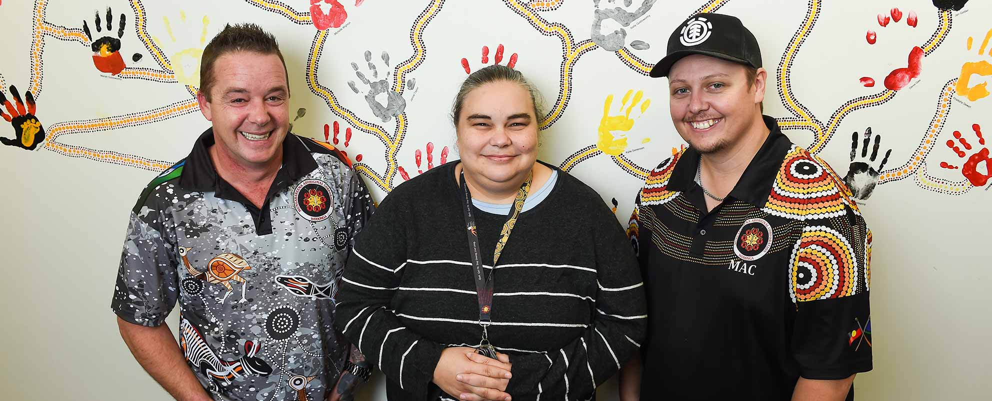 Photo of a woman and two men smiling and standing in front of wall painted with an Indigeneous design of handprints and connecting dotted lines, both men wearing polo shirts with Indigeneous designs and the woman wearing a grey sweater with thin white stripes, her hands clasped in front of her.