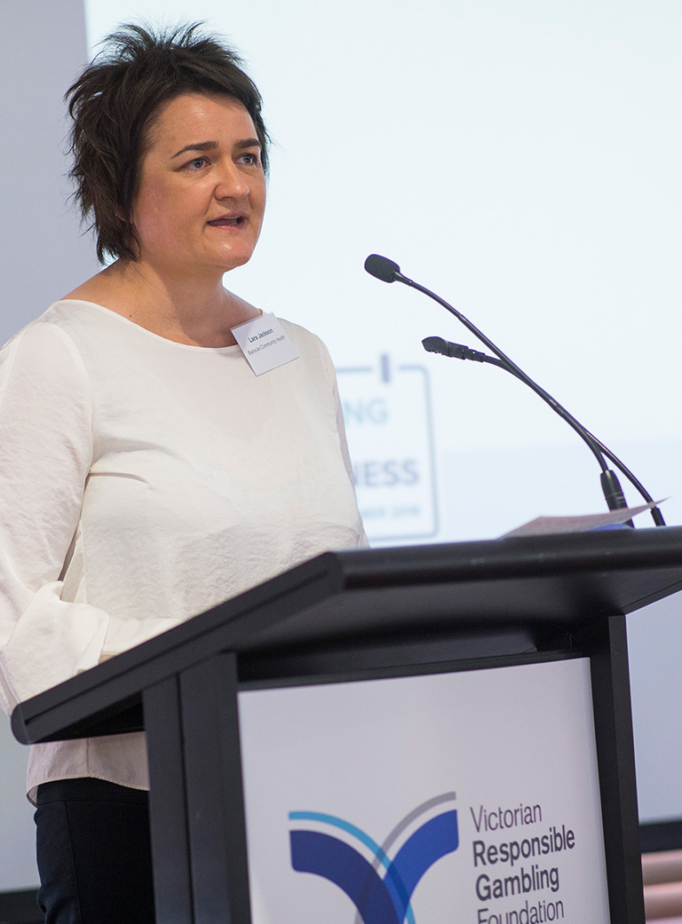 Photo of a woman with short dark hair and a serious expression, wearing a white top speaking into a microphone at a lectern bearing the Victorian Responsible Gambling Foundation logo.