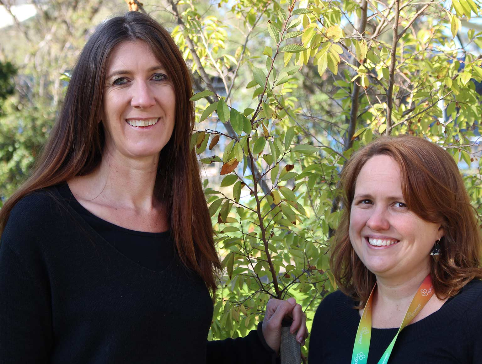 Two women in black smiling at the camera in front of some greenery, one tall with long hair while the shorter woman has red hair.
