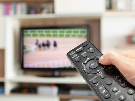 Hand operating remote control in foreground with horseracing on a TV in the background