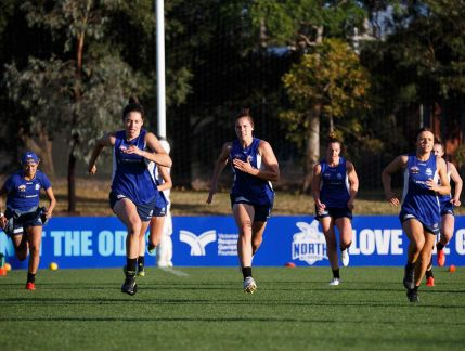 Photo of seven AFL Women's players in North Melbourne singlets running on a sporting ground towards the camera