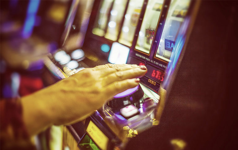 Woman's hand playing the pokies