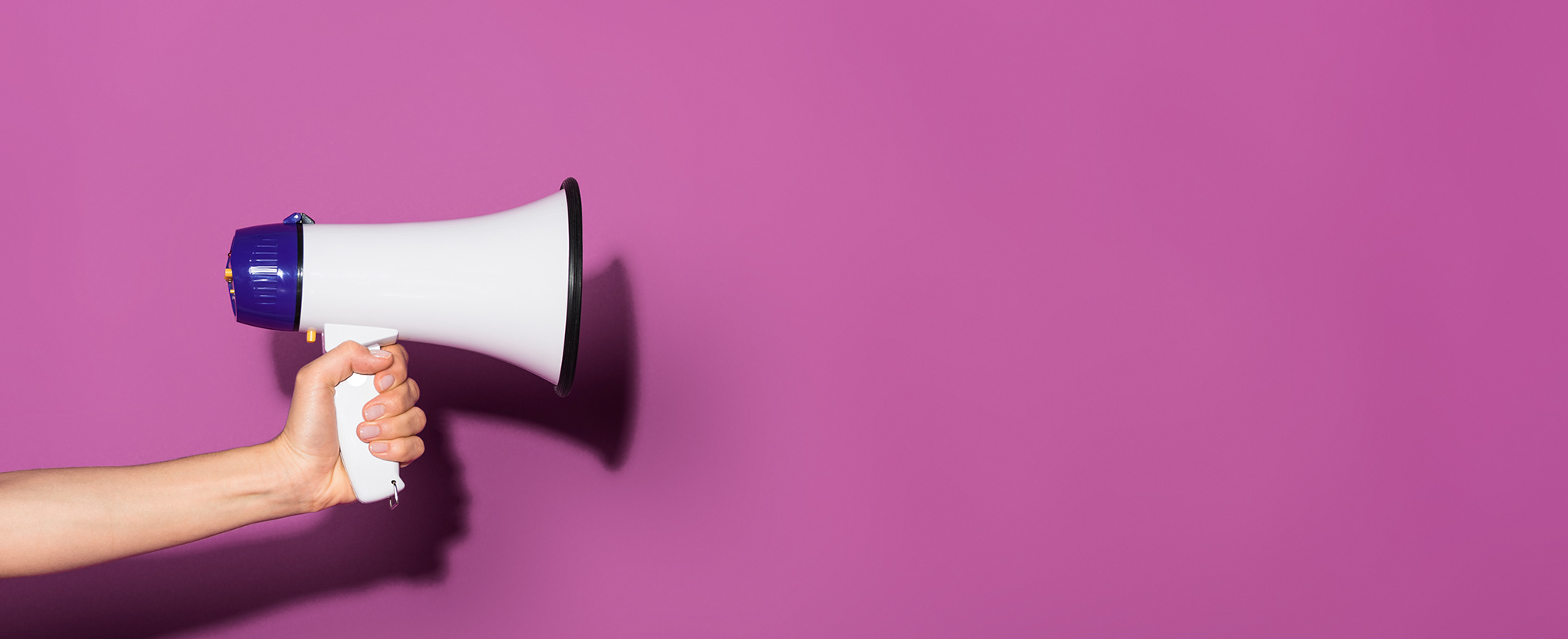 Photo of a woman's hand holding a white megaphone against a pink background