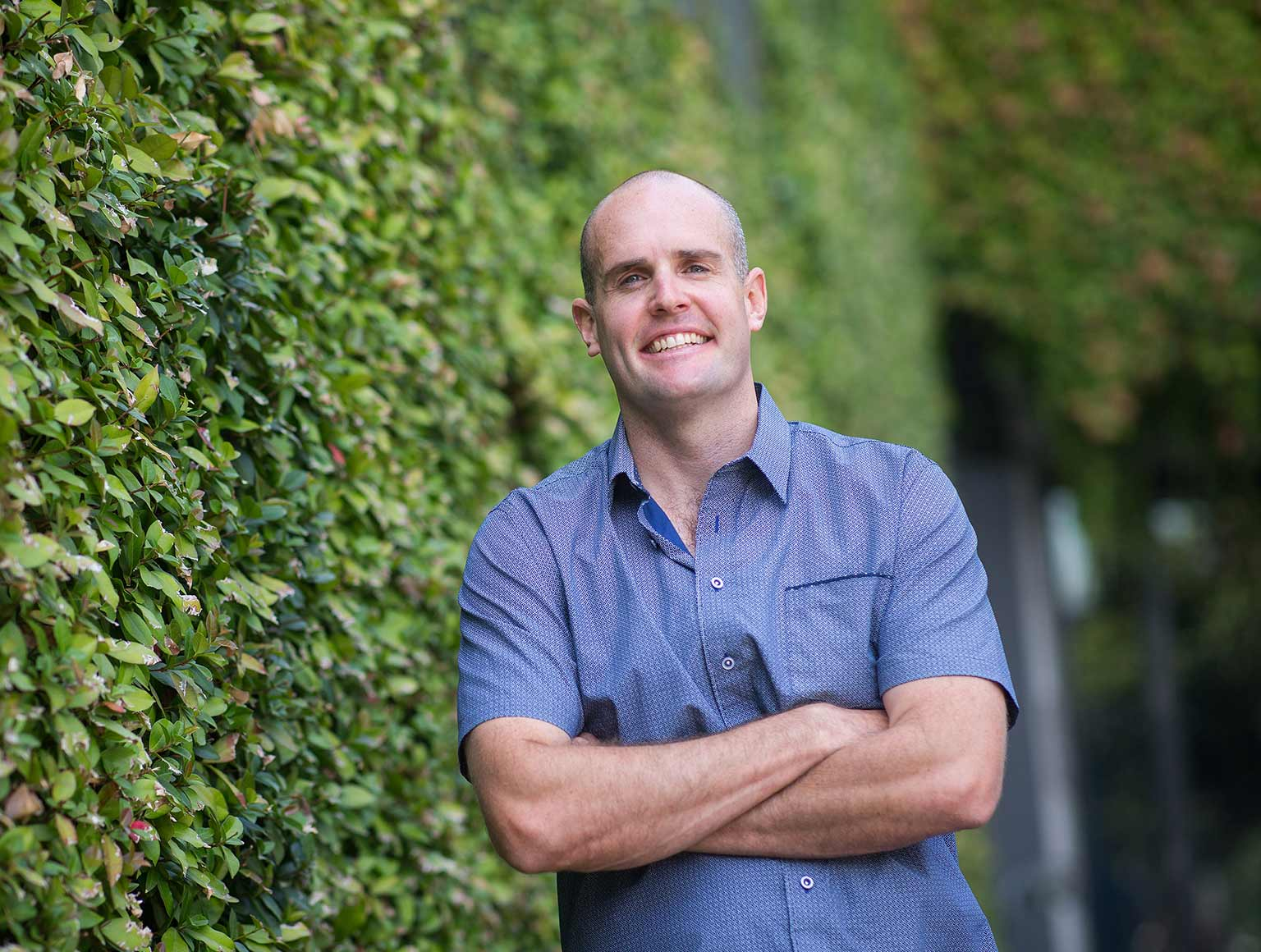 Middle-aged man in a blue shirt stands with his arms crossed beside a large hedge and smiles broadly at the camera.
