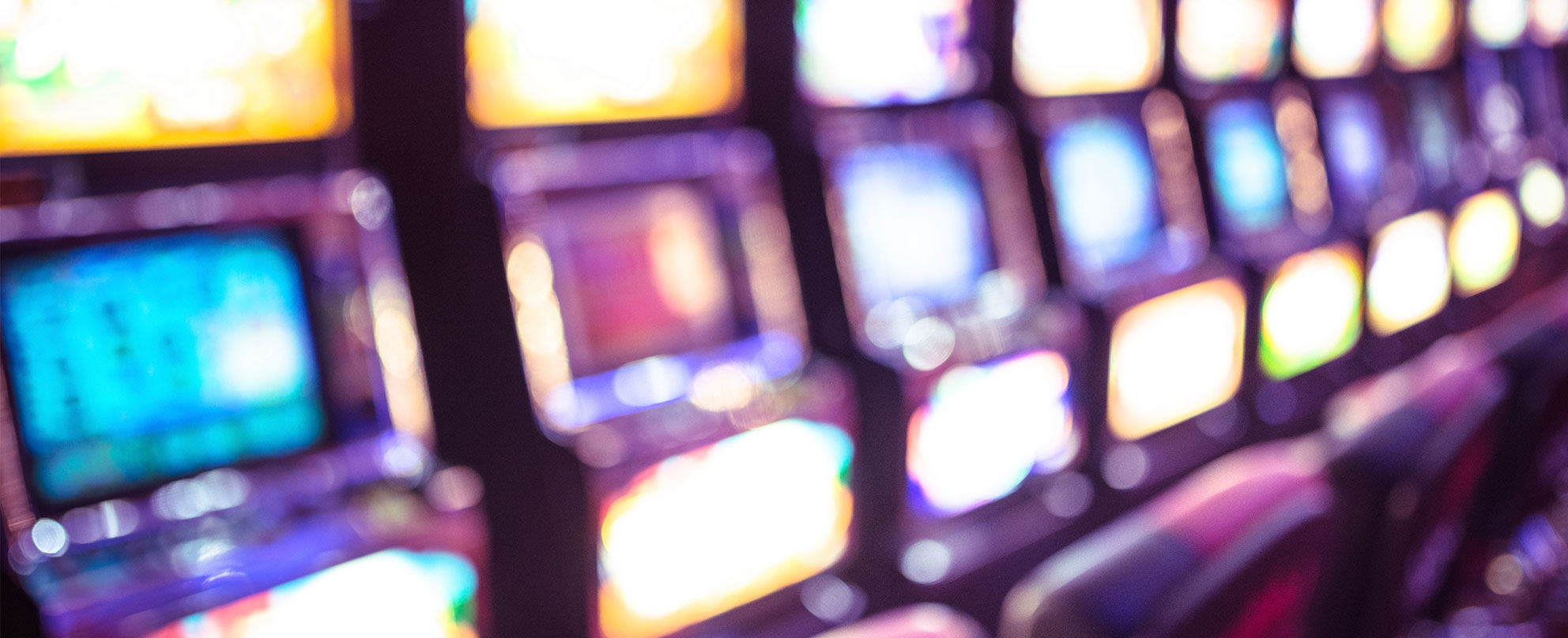 Blurred row of lit up poker machines