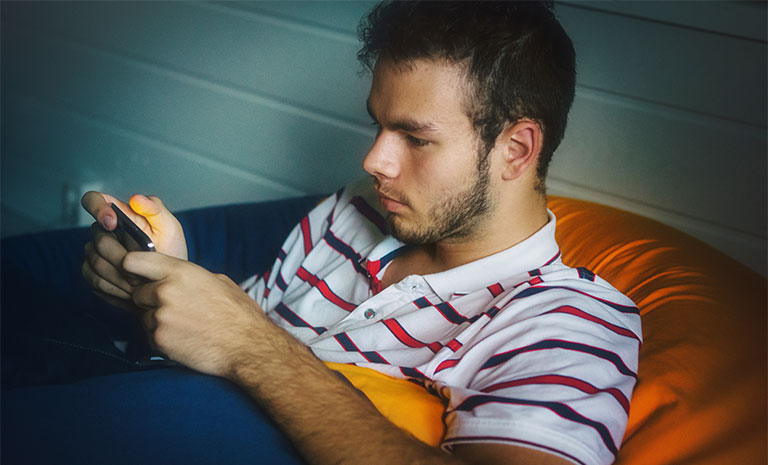 Boy sits on couch engrossed in his smart phone