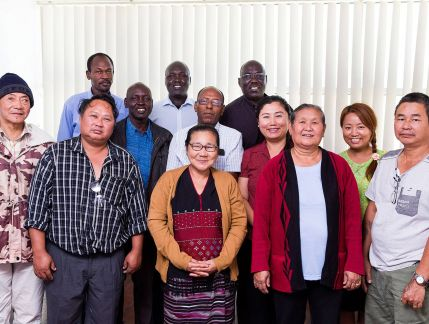A group of eight men and four women from South Sudan, Ethiopia, Somalia and Burma, standing smiling in a room