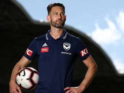 Photo of man in his thirties with short dark hair and close-cropped beard wearing a blue sports shirt and holding a soccer ball under his arm, looking off to his left with a serious expression, a stadium in the background.
