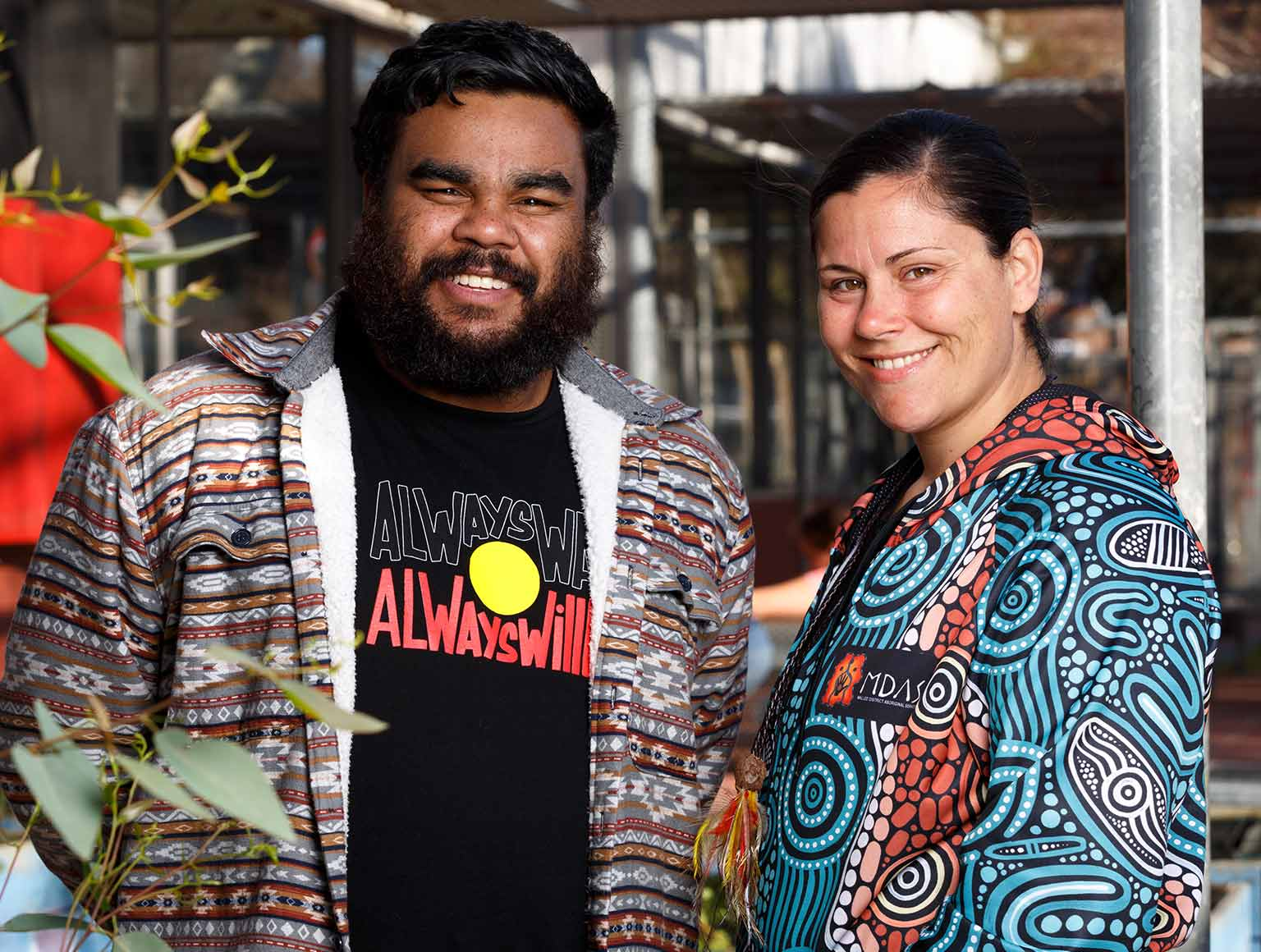 Photo of smiling older man with bald head, wearing a black polo shirt featuring Aboriginal designs, a street with cars behind and a building with a mural that says: Many, many years ago, some Elders decided that their people needed a meeting place.