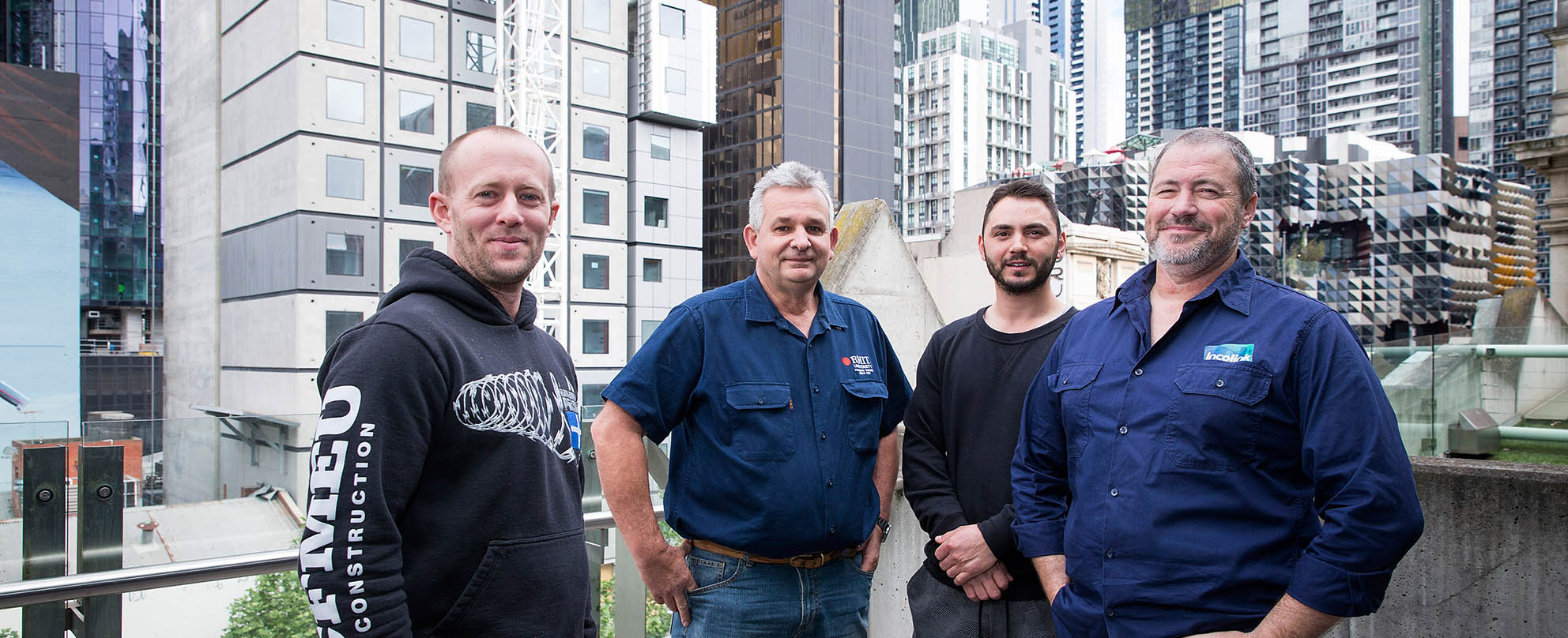 Four men standing smiling on a city balcony with skyscrapers and construction work behind them