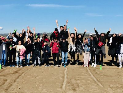 Photo of a large group of young Karen people standing in a wide row on a large expanse of sand, smiling and waving at the camera, some posing and jumping, a middle-aged woman standing and on the end at the right, also smiling and waving, hills and blue sky behind.